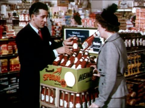 1951 Medium shot pan woman talking to Heinz ketchup salesman in supermarket / zoom in display of ketchup bottles / AUDIO