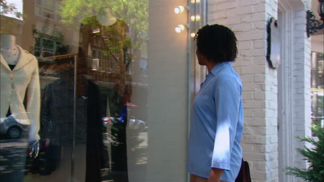 vidéos et rushes de medium shot pan woman walking up to clothing shop and looking at window display/ westfield, new jersey - une seule femme d'âge moyen