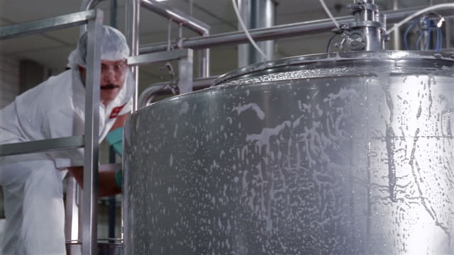 Medium shot pan workers scrubbing and rinsing tank at a water purification plant / San Antonio, Texas