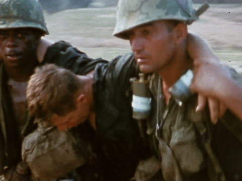 medium shot pan wounded man being held up by fellow us servicemen as he walks / vietnam - vietnam war stock videos & royalty-free footage