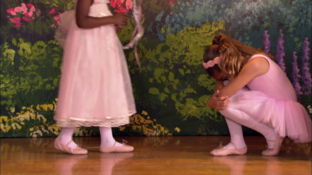 vídeos y material grabado en eventos de stock de medium shot pan young ballerina crouched down on stage / another girl tapping her with wand / ballerina dancing around younger girl - agacharse