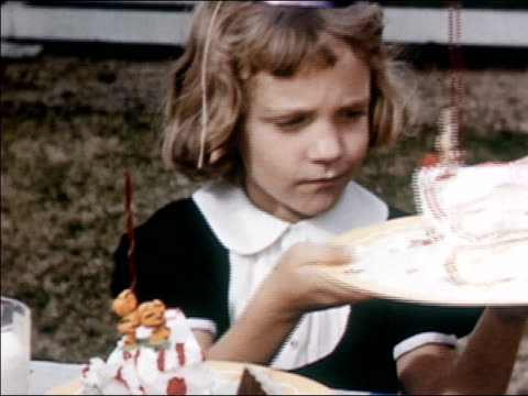 1954 medium shot pan young blonde girl eating ice cream and passing piece of cake to young brunette girl at birthday party / audio - eating utensil stock videos & royalty-free footage
