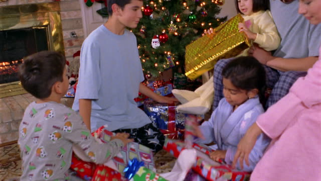 vídeos y material grabado en eventos de stock de medium shot pan young family opening christmas presents in front of christmas tree on christmas morning - familia con cuatro hijos