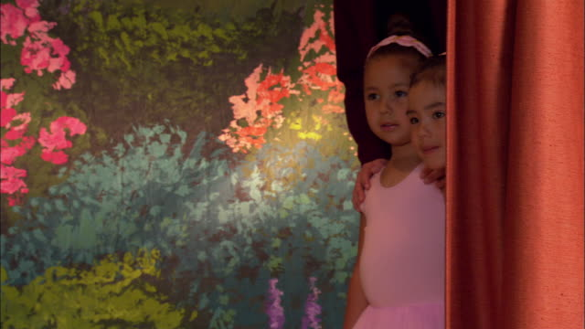 Medium shot pan young girls in tuts peeking out from behind curtain on stage at ballet recital