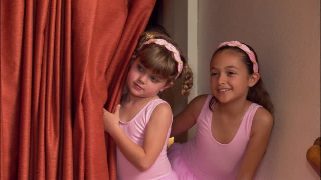 medium shot pan young girls in tutus peeking out from behind curtain on stage / smiling at camera - pacific islander background stock videos & royalty-free footage