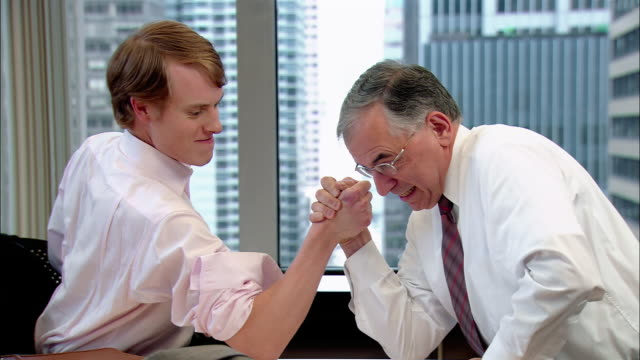 medium shot pan young man arm wresting businessman in office/ older man winning and putting arms up in victory/ new york, new york - arm wrestling stock videos & royalty-free footage