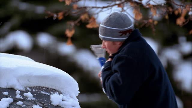 vídeos de stock, filmes e b-roll de medium shot pan young man scraping snow and ice off car windshield / utah - tossindo