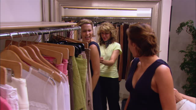 1d6a2f79c00 Medium Shot Pan Young Woman Trying On Dress In Clothing Shop With Mother  Mother Hugging Daughter Daughter Putting Hands On Face Westfield New Jersey  Stock ...