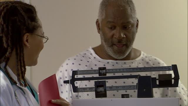 Medium shot panning doctor weighing man wearing hospital gown