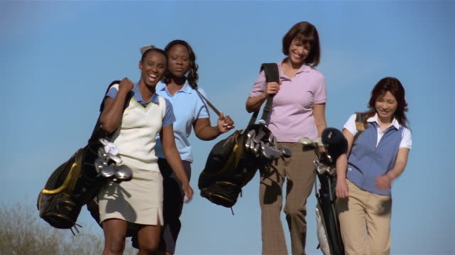 Medium shot panning four women golfers carrying clubs and walking