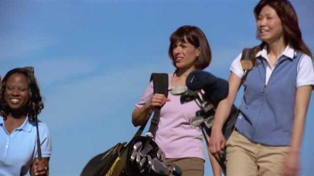 vídeos de stock, filmes e b-roll de medium shot panning four women golfers carrying clubs and walking - bolsa de golfe