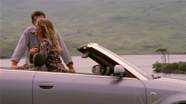 medium shot panning man hugging woman in convertible / couple laughing / scotland - 年の差カップル点の映像素材/bロール