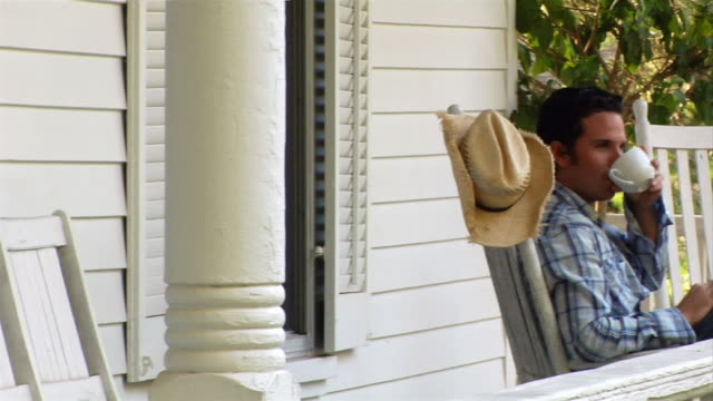 stockvideo's en b-roll-footage met medium shot panning man sitting in rocking chair on porch of country house and drinking coffee - schommelen schommelstoel