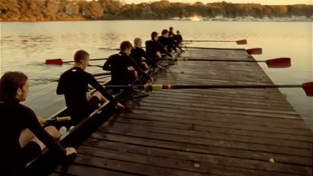 medium shot panning members of rowing team pushing off from dock - einzelne frau mit männergruppe stock-videos und b-roll-filmmaterial