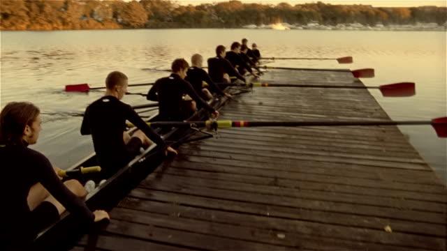 Medium shot panning members of rowing team pushing off from dock