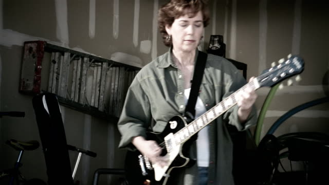 medium shot panning middle-aged woman playing guitar in garage band - rocking stock videos & royalty-free footage