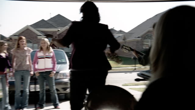 Medium shot panning three teenage girls dancing and clapping as they watch rock band of middle age women performing in garage