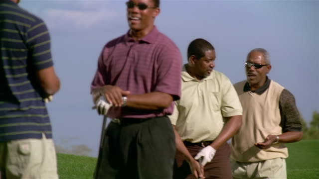 medium shot panning two pairs of men talking on driving range - golf glove stock videos and b-roll footage