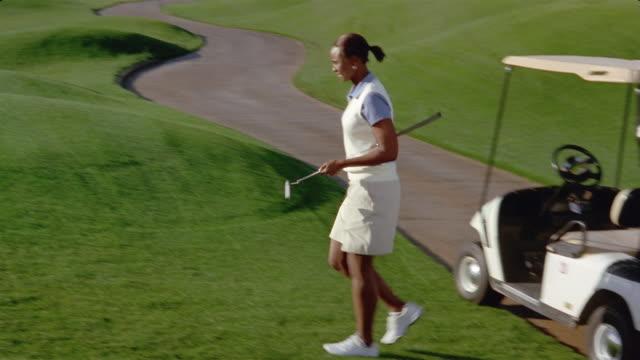 vídeos de stock, filmes e b-roll de medium shot panning woman taking golf club from bag on cart / wide shot golfer walking across course to green - bolsa de golfe
