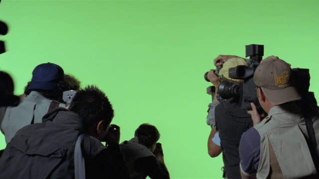 medium shot paparazzi taking photos against green screen background/ los angeles - roter teppich stock-videos und b-roll-filmmaterial