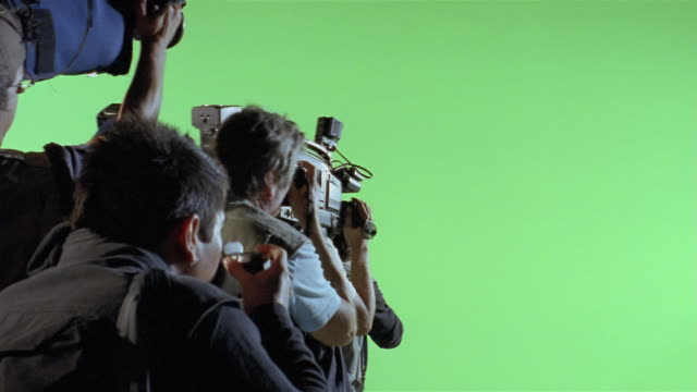 Medium shot paparazzi taking photos against green screen background/ Los Angeles