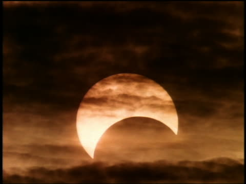 medium shot partial solar eclipse with wispy clouds in foreground - controluce video stock e b–roll