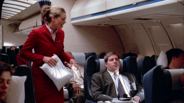 Medium shot passengers sleeping on airplane / flight attendant offers man pillow