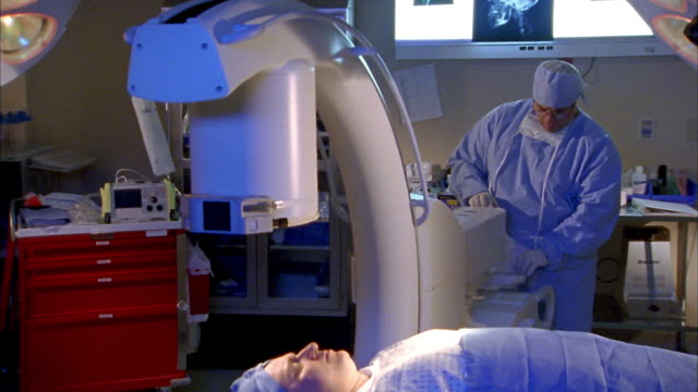 Medium shot patient on surgical table in foreground / doctor in surgical scrubs adjusting medical equipment
