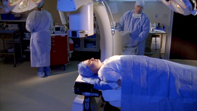 Medium shot patient on surgical table in foreground / doctors working w/medical equipment in background