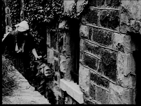 1916 B/W Medium shot peasant woman sneaking along side of building