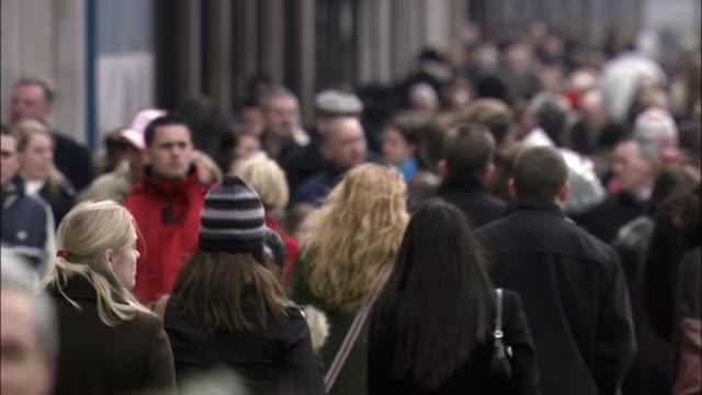Medium shot pedestrians on crowded city street/ London