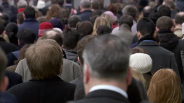 Medium shot pedestrians on crowded city street walking away from camera/ London