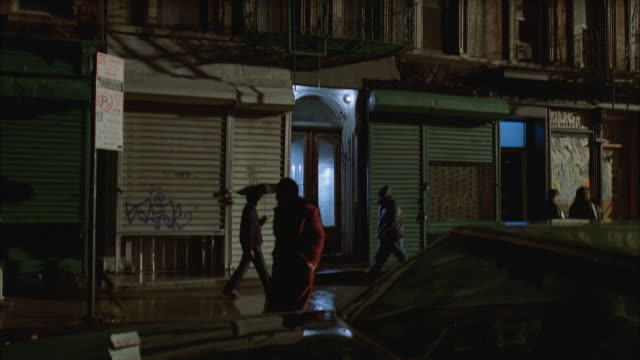 medium shot pedestrians passing by door of apartment building in rain / tilt up tilt down facade / lower east side, nyc - fensterfront stock-videos und b-roll-filmmaterial
