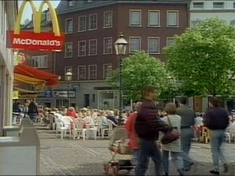 1994 medium shot pedestrians walking past diners seated in plaza outside mcdonald's / aachen, germany / audio - mcdonald's stock videos & royalty-free footage