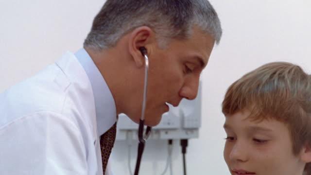 stockvideo's en b-roll-footage met medium shot pediatrician examining boy with stethoscope - ontbloot bovenlichaam