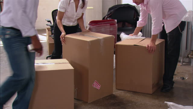 medium shot people and boxes in loft office space/ tilt up pan people moving box as woman holds up plastic bag/ brooklyn, new york - pushing stock videos & royalty-free footage