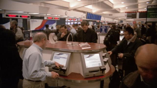 Medium shot people at electronic ticket kiosk / Hartsfield Airport, Atlanta