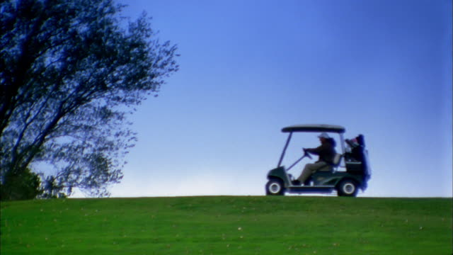vidéos et rushes de medium shot people driving golf carts on golf course along horizon - golf