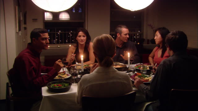 Medium shot people eating and talking during dinner party