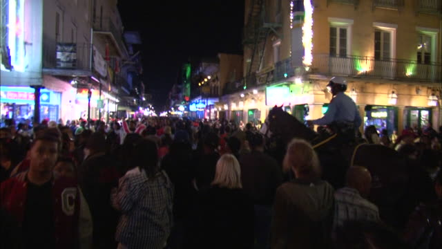 medium shot - people milling about on bourbon street at night; policeman on horse makes his way through the crowd / new orleans louisiana - bourbon street new orleans stock videos and b-roll footage