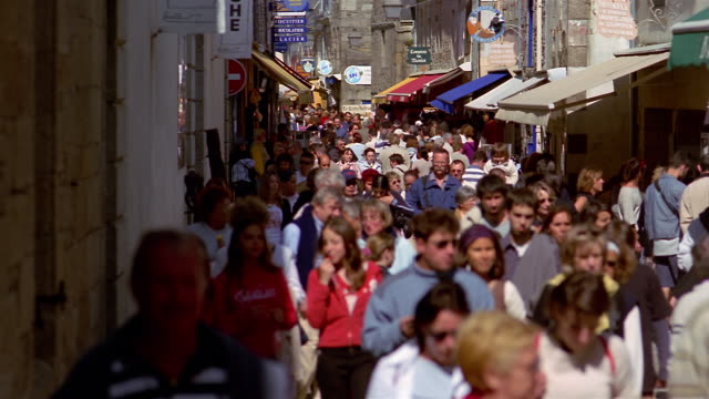 medium shot people walking along crowded town street / concarneau - village stock videos & royalty-free footage
