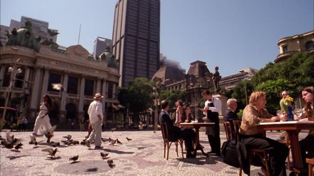 vídeos de stock, filmes e b-roll de medium shot people walking in square and sitting at outdoor cafes / rio de janeiro - praça