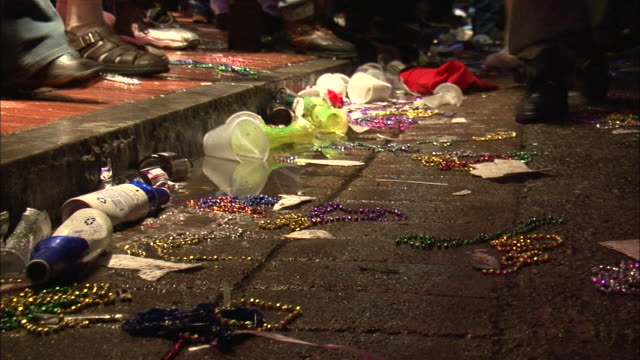 vidéos et rushes de medium shot - people walking near trash strewn about edge of sidewalk; mostly cups, bottles, and colored plastic beads / new orleans louisiana - trottoir