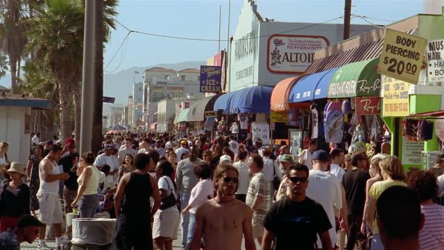 medium shot people walking on boardwalk at venice beach / los angeles - venice beach stock videos & royalty-free footage