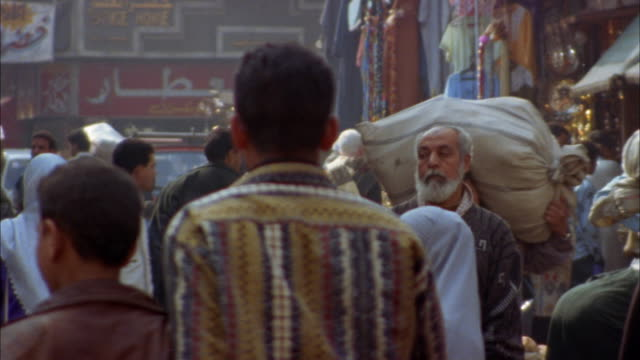 Medium shot people walking through crowded street bazaar in old section / Cairo, Egypt