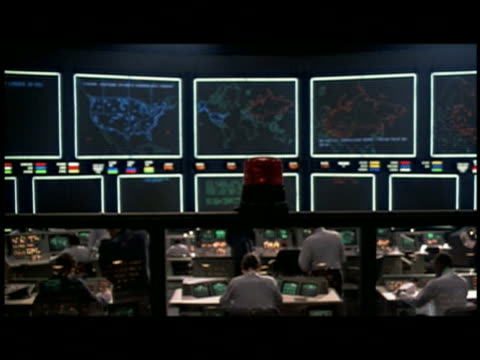 Medium shot people working in dark control room w/maps on screen in background / red light flashes in foreground