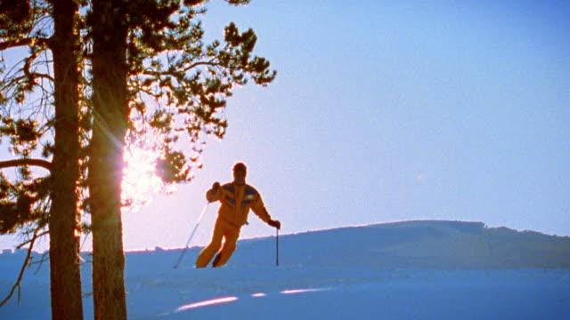 vídeos de stock e filmes b-roll de medium shot person skiing over small mountain drifts and past trees toward camera / silver creek, colorado - roupa de esqui