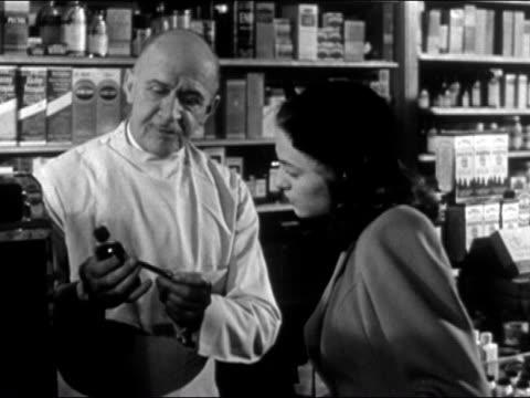 1948 medium shot pharmacist explaining bottle of medication to female customer/ pharmacist polishing bottle with hand and smiling - prelinger archive video stock e b–roll