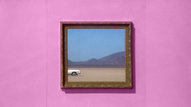 Medium shot picture frame showing desert scene on pink wall / moving convertible appearing in frame