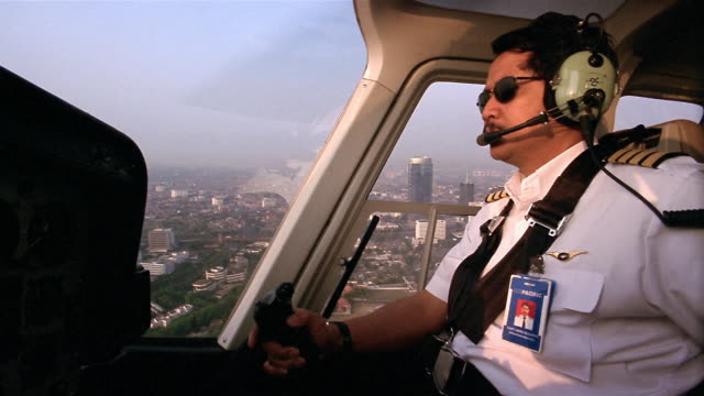 Medium shot pilot in cockpit flying helicopter and looking out over Jakarta / Indonesia